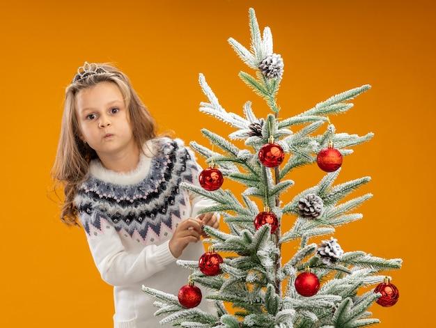 Blij meisje dat zich achter de kerstboom bevindt die tiara met slinger op hals draagt die op oranje achtergrond wordt geïsoleerd