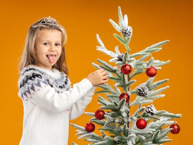 Blij meisje dat zich dichtbij kerstboom bevindt die tiara met slinger op hals draagt, hangt stuk speelgoed aan de boom die op oranje achtergrond wordt geïsoleerd