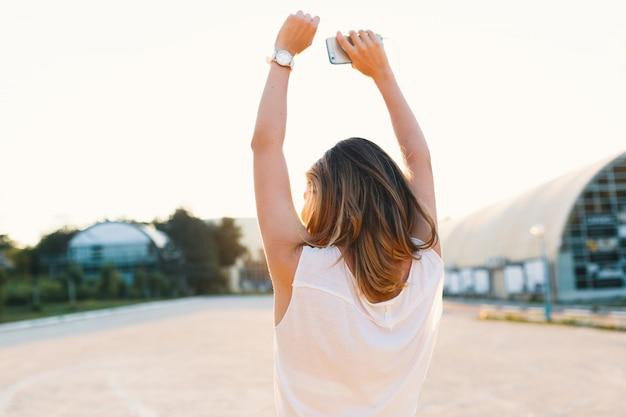Blij meisje die in de straat op een zonnige dagholdings omhoog dansen