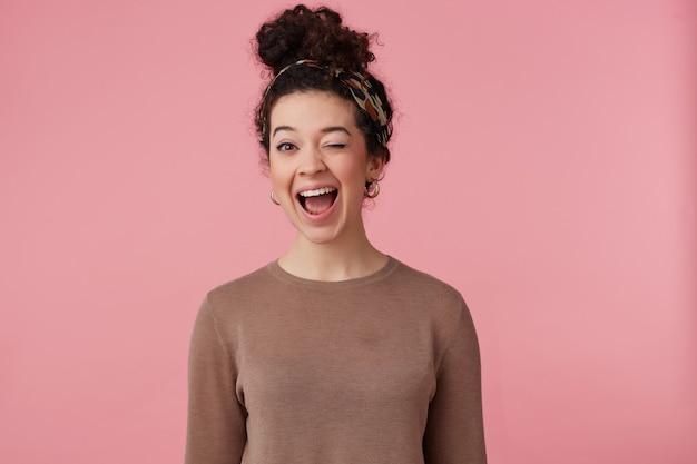 Blij meisje, gelukkig ogende vrouw met donker krullend haarbroodje. met hoofdband, oorbellen en bruine trui. heeft make-up. emotie concept