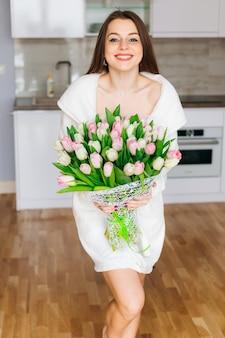 Blij meisje in de keuken met een boeket roze en witte tulpen thuis, vreugde en glimlach. gelukkige moederdag! perfecte ochtend.