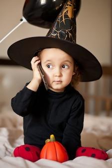 Blij meisje in een heksenkostuum dat smartphone houdt en spreekt. halloween online groeten.