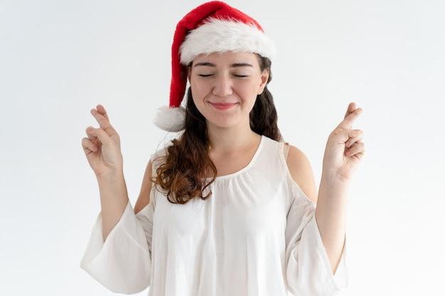 Blij meisje in kerstmishoed die wens maken