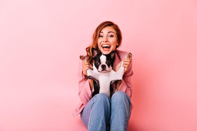 Blij meisje in spijkerbroek spelen met grappige kleine hond. indoor portret van opgewonden gember dame met krullend kapsel tijd doorbrengen met haar puppy.