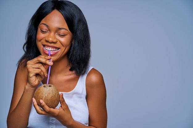 Blij meisje in witte bovenkant drinkt uit een kokosnoot met een rietje. dieet concept