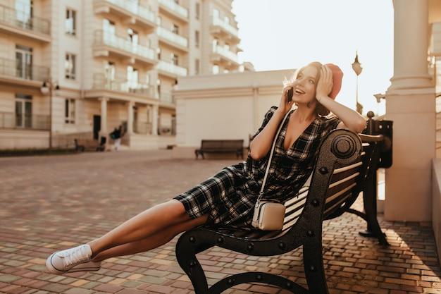 Blij meisje in witte sneakers zittend op een bankje in de avond. buiten foto van geweldige brunette dame praten over de telefoon op straat.
