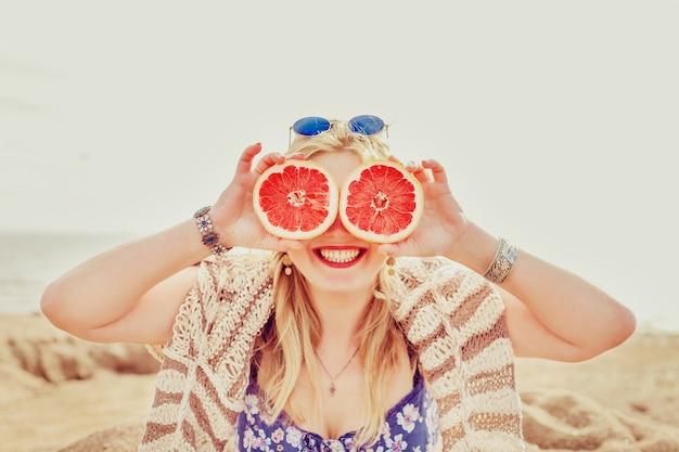 Blij meisje met een halve grapefruit.