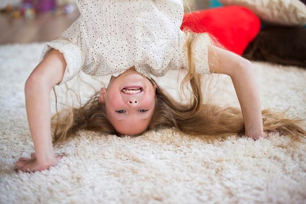 Blij meisje met een headstand-pose