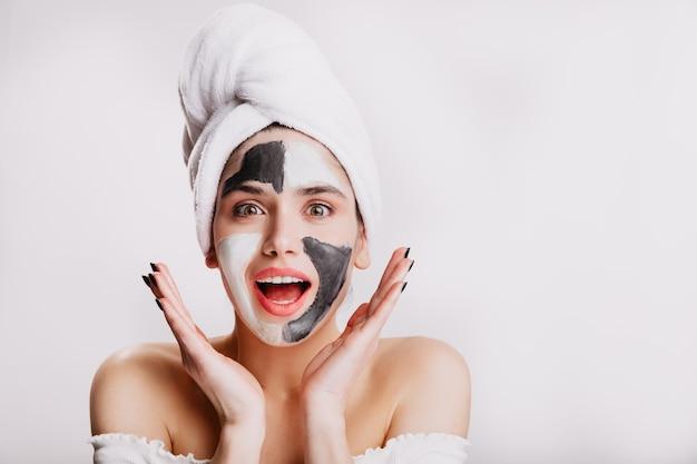Blij meisje met gezichtsmasker van verbazing. groenogige vrouw die zich voordeed op witte muur na het wassen van haar haar.