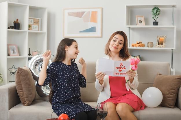 Blij meisje met ja gebaar moeder die een wenskaart vasthoudt en leest terwijl ze op de bank zit op een gelukkige vrouwendag in de woonkamer