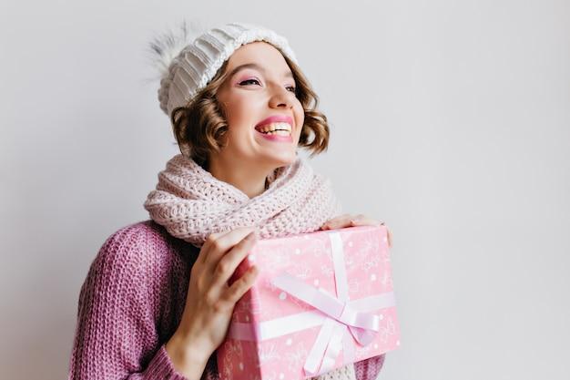 Blij meisje met kort kapsel genieten van wintervakantie met cadeautjes. indoor portret van mooie jonge vrouw in trui en sjaal met nieuwe jaar cadeau op witte muur.