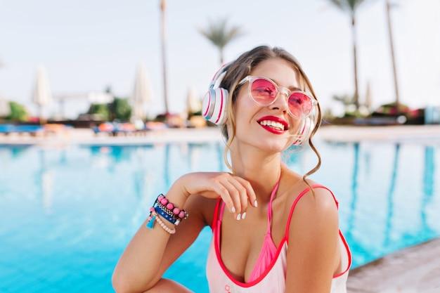 Blij meisje met lichte make-up en kleurrijke accessoires die genieten van zuidelijk landschap terwijl ze naar muziek luistert