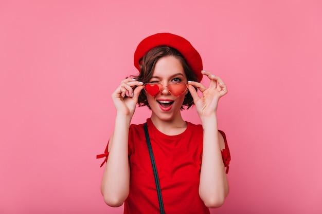 Blij meisje met plezier gewijd aan valentijnsdag. binnenfoto van grappige krullende franse vrouw.