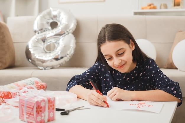 Blij meisje op gelukkige vrouwendag schrijft op ansichtkaart zittend op de vloer achter de salontafel met cadeautjes in de woonkamer