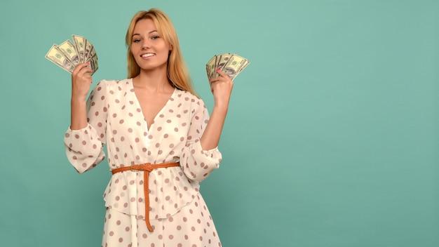 Blij meisje won de loterij en houdt een fan van amerikaanse dollars in haar handen op een blauwe achtergrond - afbeelding