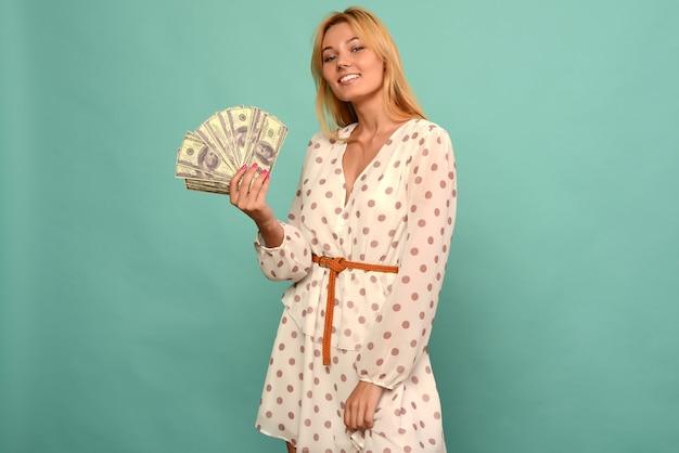 Blij meisje won de loterij en houdt een fan van amerikaanse dollars in haar handen op een blauwe achtergrond