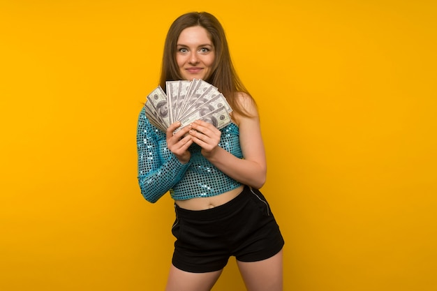 Blij meisje won de loterij en houdt een fan van amerikaanse dollars in haar handen op een gele achtergrond