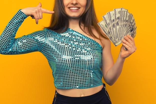 Blij meisje won de loterij en wees op een fan van amerikaanse dollars in haar handen op een gele achtergrond