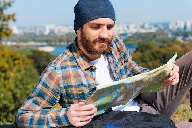 Blij met de route. glimlachende jonge man die in de buurt van een rugzak zit en een kaart vasthoudt en er doorheen kijkt