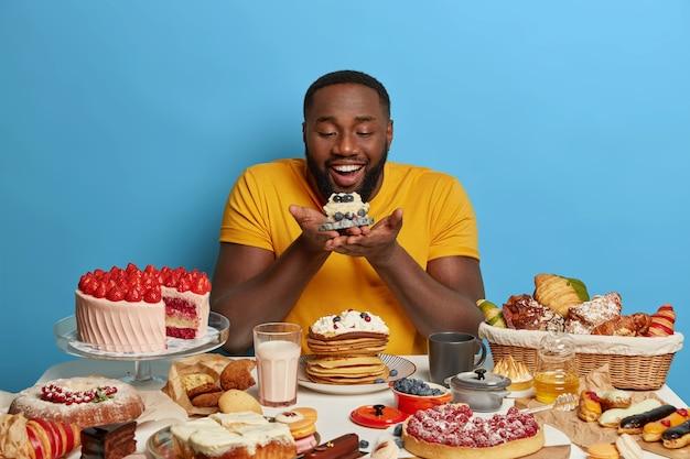 Blij met een donkere huid zoetekauw man houdt een kleine cupcake, kijkt gelukkig naar een heerlijk dessert, draagt een gele t-shirt, poseert tegen een blauwe achtergrond