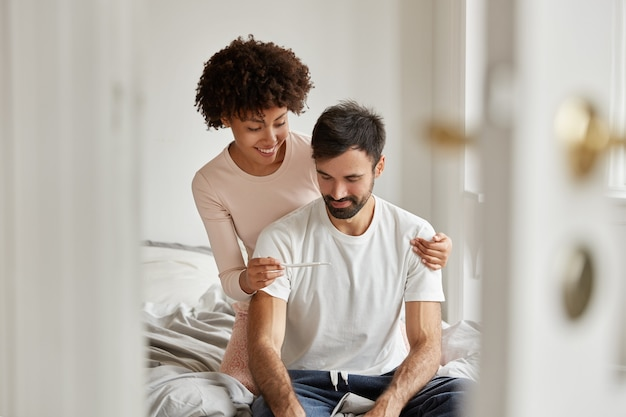 Blij met een donkere huidskleur die het resultaat van de zwangerschap thuis aan haar vriendje laat zien, een glimlach op het gezicht heeft, gekleed in vrijetijdskleding, poseert in een gezellige slaapkamer. het familiepaar verheugt zich samen over nieuws over zwangerschap.