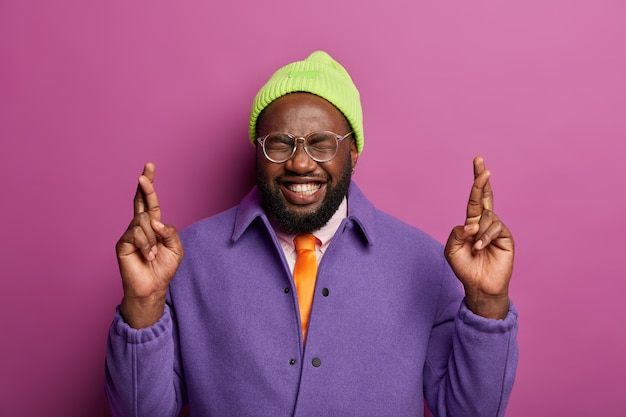 Blij met een donkere huidskleur staat met gekruiste vingers, heeft een wens voor beter, lacht kieskeurig, draagt een hoed en een paars jasje, is bijgelovig