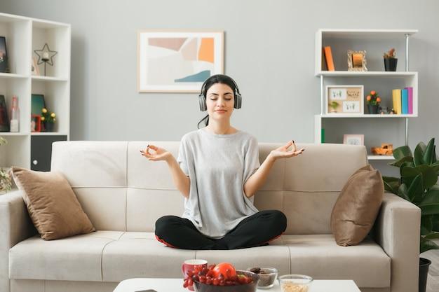 Blij met een jong meisje met gesloten ogen dat een koptelefoon draagt en mediteert op de bank achter de salontafel in de woonkamer