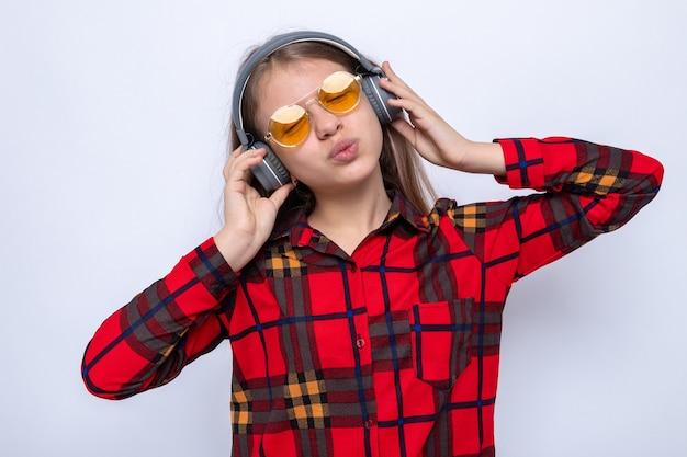 Blij met gesloten ogen die het hoofd kantelen, mooi klein meisje met een rood shirt en een bril met koptelefoon