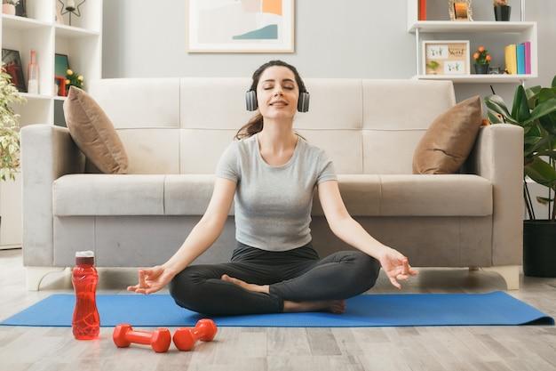Blij met gesloten ogen jong meisje met koptelefoon die traint op yogamat voor de bank in de woonkamer