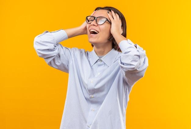 Blij met gesloten ogen, jong mooi meisje met een bril greep het hoofd geïsoleerd op een oranje muur
