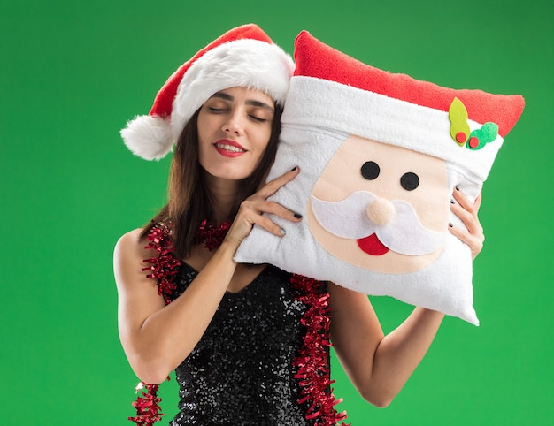 Blij met gesloten ogen jong mooi meisje met kerstmuts met slinger op nek kerst kussen geïsoleerd op groene muur te houden