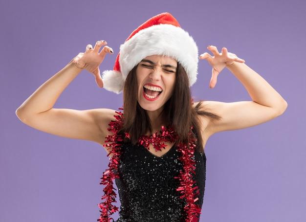 Blij met gesloten ogen jong mooi meisje met kerstmuts met slinger op nek met tijger stijl gebaar geïsoleerd op paarse achtergrond