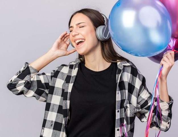 Blij met gesloten ogen jong mooi meisje met koptelefoon met ballonnen