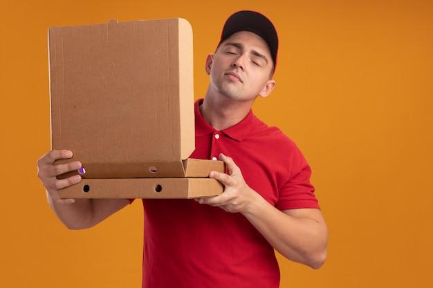 Blij met gesloten ogen jonge bezorger in uniform met dop die opengaat en pizzadoos snuift geïsoleerd op oranje muur
