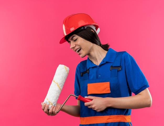 Blij met gesloten ogen jonge bouwvrouw in uniform die rolborstel vasthoudt en zingt
