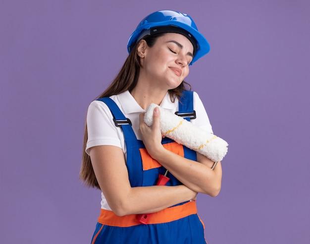 Blij met gesloten ogen jonge bouwvrouw in uniform geknuffelde rolborstel geïsoleerd op paarse muur
