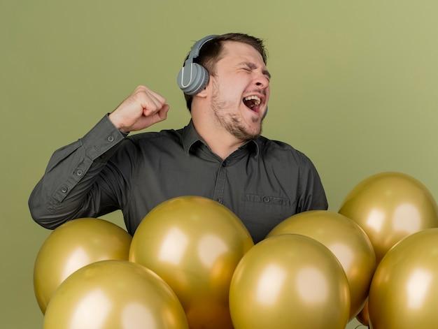 Blij met gesloten ogen jonge feest man met zwarte shirt staande onder ballonnen luisteren muziek van koptelefoon geïsoleerd op olijfgroen