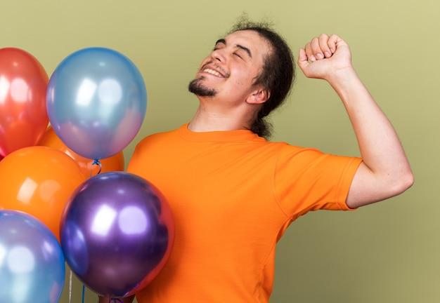 Blij met gesloten ogen jonge man met oranje t-shirt met ballonnen met ja gebaar geïsoleerd op olijfgroene muur
