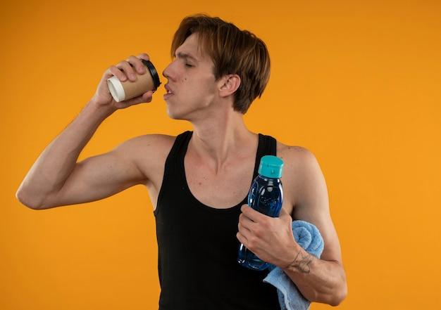 Blij met gesloten ogen jonge sportieve kerel die handdoek met waterfles houdt en koffie drinkt die op oranje muur wordt geïsoleerd