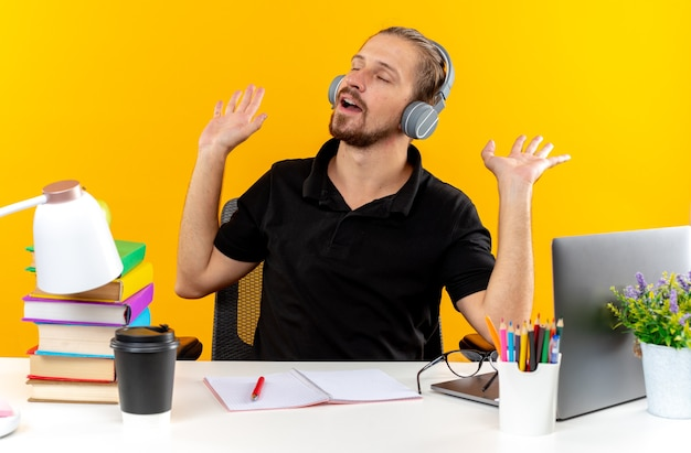 Blij met gesloten ogen, jonge student die een koptelefoon draagt die aan tafel zit met schoolhulpmiddelen die handen spreiden