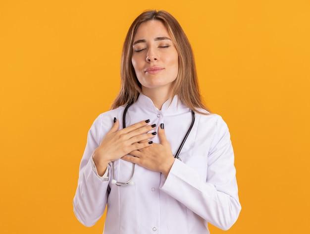 Blij met gesloten ogen jonge vrouwelijke arts die medische mantel draagt met een stethoscoop die handen op het hart legt dat op gele muur is geïsoleerd