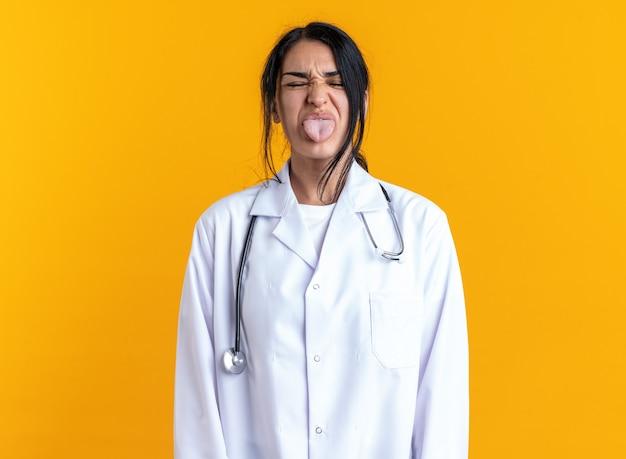 Blij met gesloten ogen jonge vrouwelijke arts die medische mantel draagt met een stethoscoop die tong toont die op gele muur is geïsoleerd