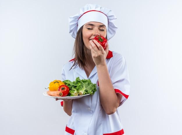 Blij met gesloten ogen jonge vrouwelijke kok in uniform van de chef-kok met groenten op bord snuivende peper geïsoleerd op een witte muur