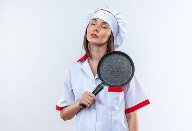 Blij met gesloten ogen jonge vrouwelijke kok in uniform van de chef-kok met koekenpan geïsoleerd op een witte achtergrond