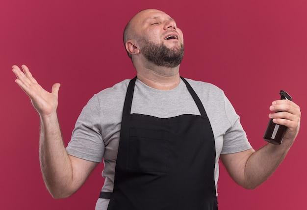 Blij met gesloten ogen mannelijke kapper van middelbare leeftijd in uniform met spuitfles die hand spreidt geïsoleerd op roze muur