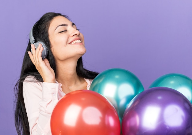 Blij met gesloten ogen met koptelefoon, mooi meisje met ballonnen