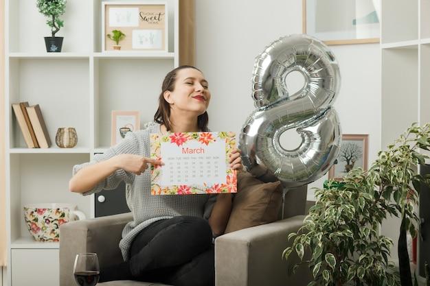Blij met gesloten ogen, mooi meisje op gelukkige vrouwendag en wijst naar kalender zittend op een fauteuil in de woonkamer