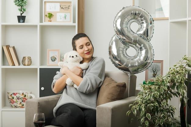 Blij met gesloten ogen mooie vrouw op gelukkige vrouwendag met teddybeer zittend op fauteuil in woonkamer