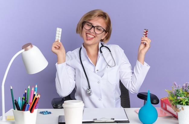Blij met gesloten ogen zit een jonge vrouwelijke arts met een medisch gewaad met een stethoscoop en een bril aan tafel met medische hulpmiddelen die pillen vasthouden en tong geïsoleerd op een blauwe muur tonen