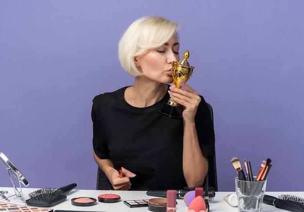 Blij met gesloten ogen zit een mooi meisje aan tafel met make-uptools die de winnaarbeker vasthouden en kussen geïsoleerd op een blauwe muur